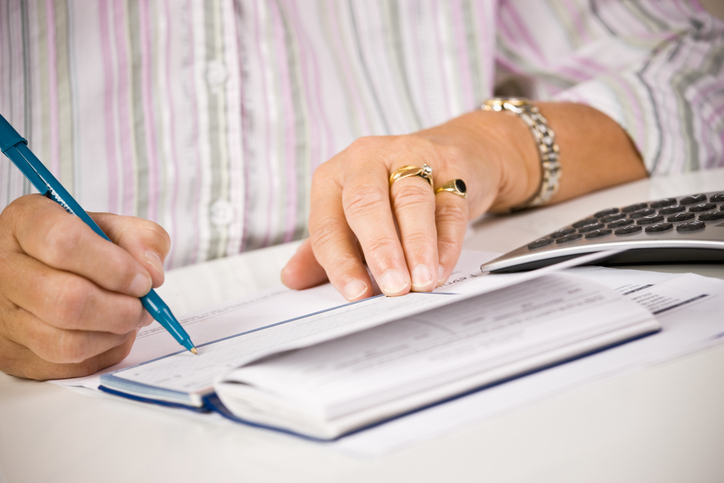 senior writing student loan check